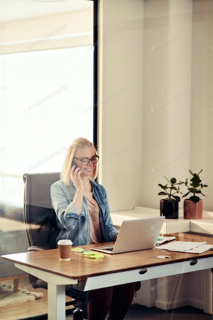 Young businesswoman talking on a cellphone in her office