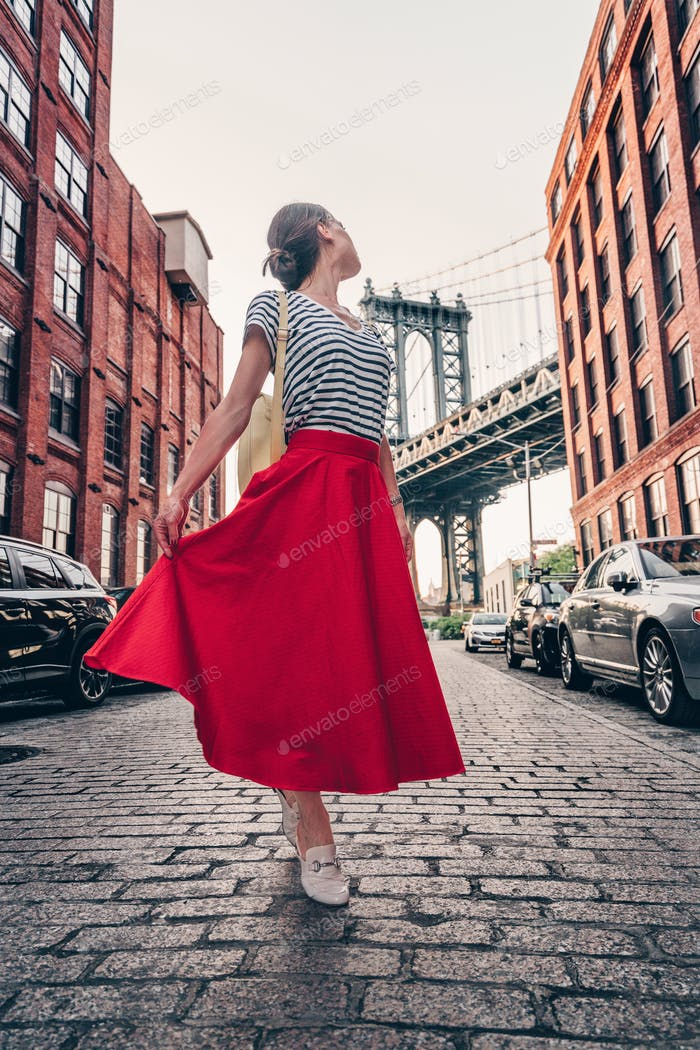 Beautiful girl in a red skirt on the background of the bridge
