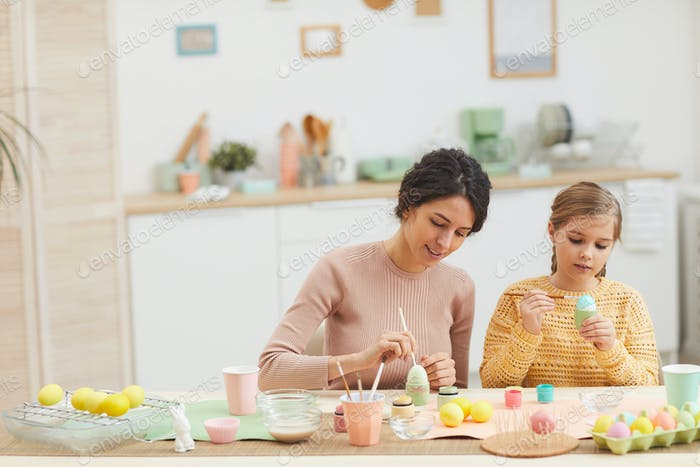 Girl Painting Easter Eggs with Mom