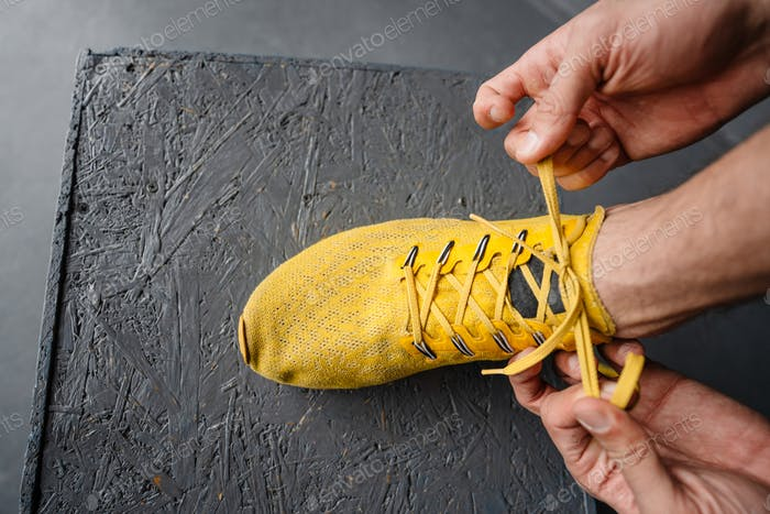 Young sportsman tying his shoe laces while working out