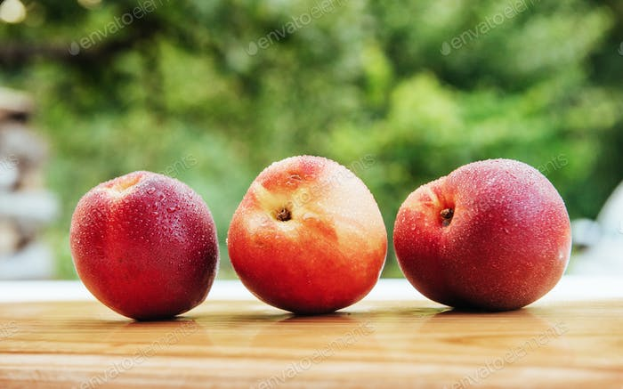 Beautiful fragrant ripe nectarines on the wooden board.