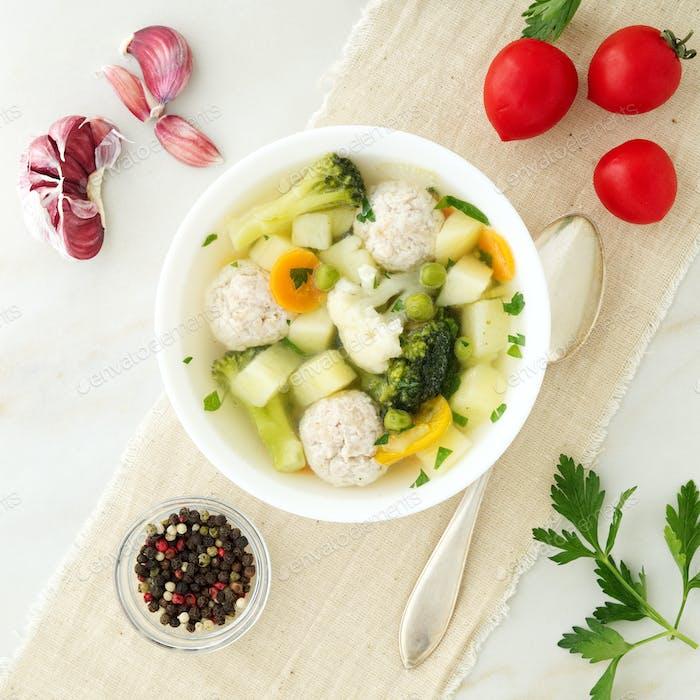 Schüssel Suppe, eine Tasse Brühe und Gemüse, Fleischbällchen aus Truthahn und Huhn, Draufsicht