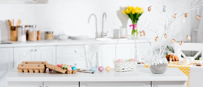 Panoramic shot of wicker basket, painted eggs and easter tree on table