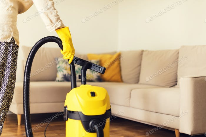 Woman cleaning sofa with yellow vacuum cleaner. Copy space. Cleaning service concept