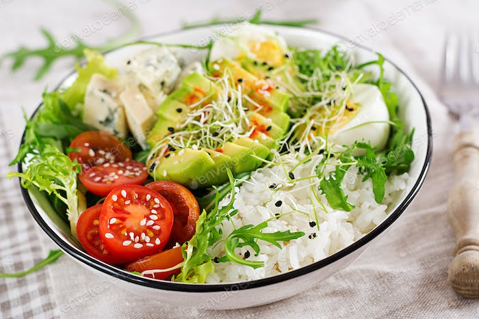 Healthy green vegetarian buddha bowl lunch with eggs, rice, tomato, avocado and blue cheese