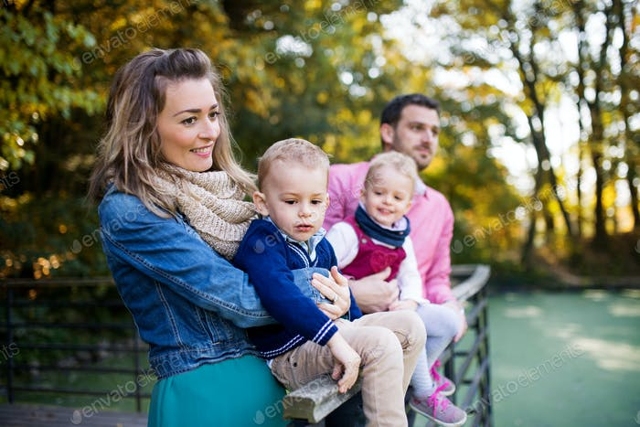 Beautiful young family with small twins on a walk in autumn park