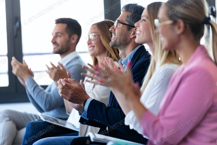 Happy business team clapping after listening the conference while sitting on coworking space.