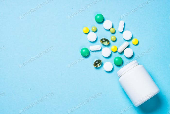 Pills, tablets and capsules on blue