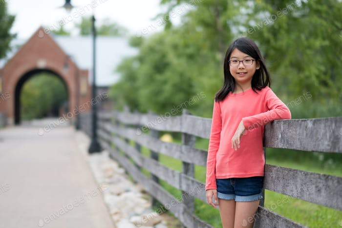 Smiling little Asian girl standing in the park
