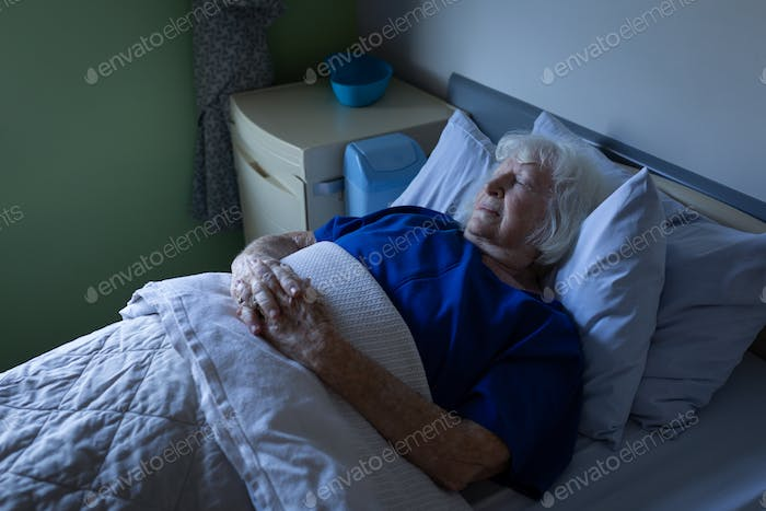 Female patient sleeping with hands joined in a hospital bed at hospital