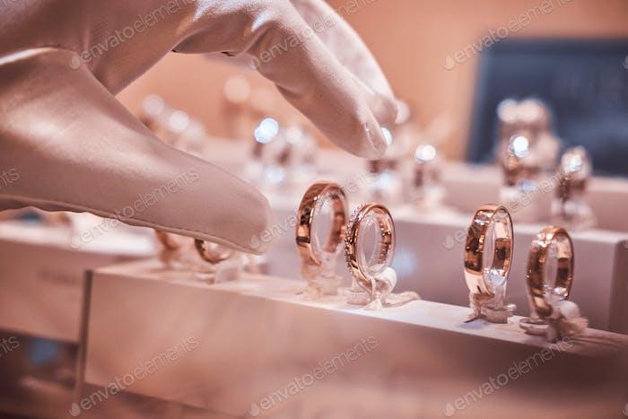 Hand-in-Handschuhe nehmen zu exklusiven Ringen auf der Vitrine eines Juweliergeschäfts