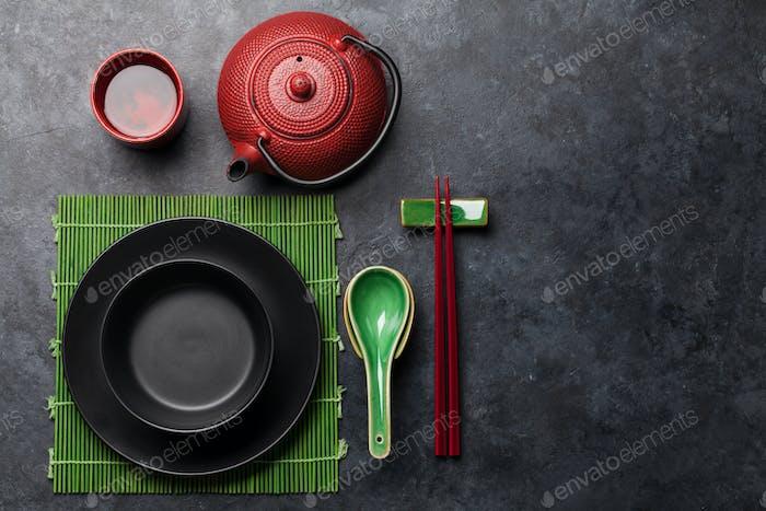 Japanischer Tee, leerer Teller und Essstäbchen