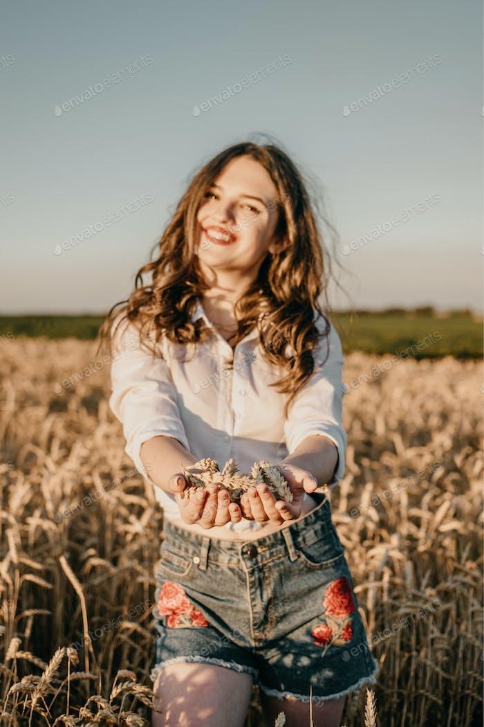 Cultivo de trigo, cosecha, cosecha agricultura, economía. Mujer joven morena con las manos llenas de madura
