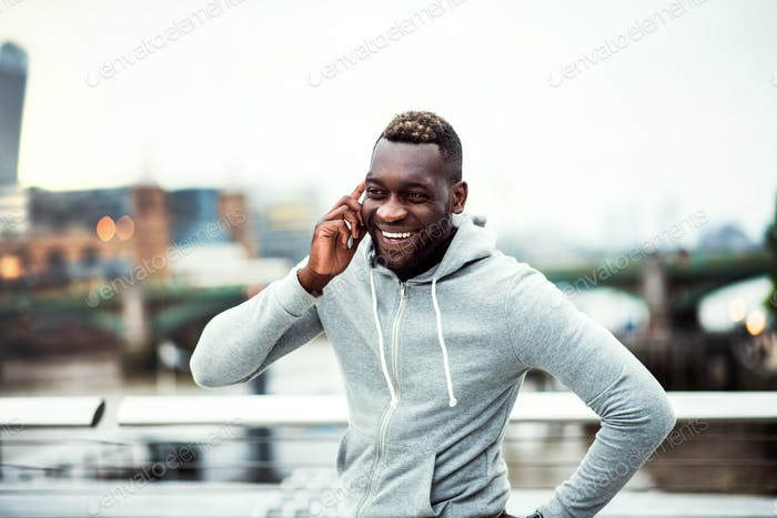 Black man runner with smartphone on the bridge in a city, making a phone call.