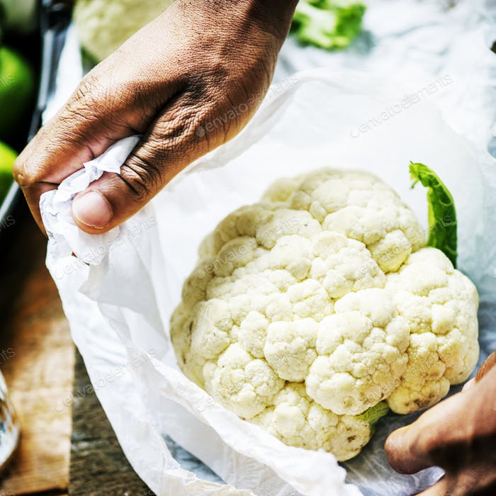 Closeup of hand with cauliflower in plastic bag