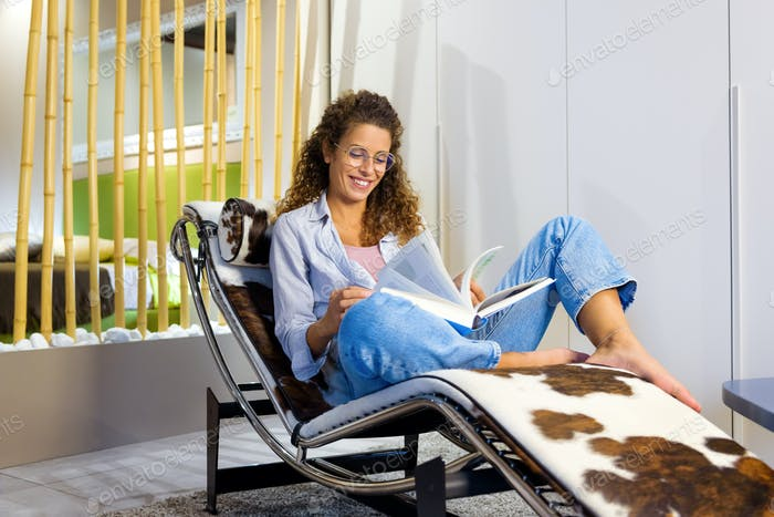 Happy contented young woman relaxing reading