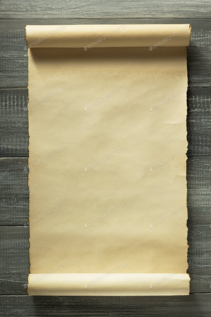 parchment scroll at wooden background