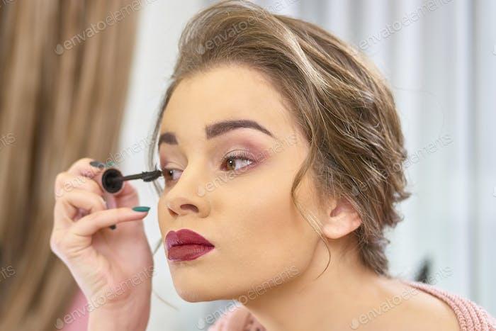 Woman using eyelash brush