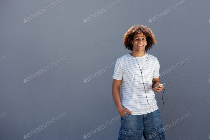 happy young man smiling with smart phone and earphones