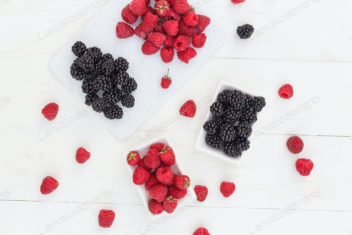 raspberries and blackberries white wooden background