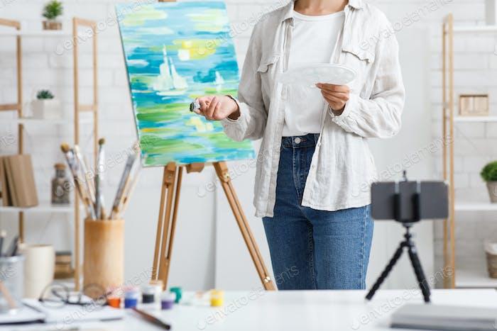 Malerei und moderne Technik. Mädchen mit Pinsel und Farben malen zu Hause