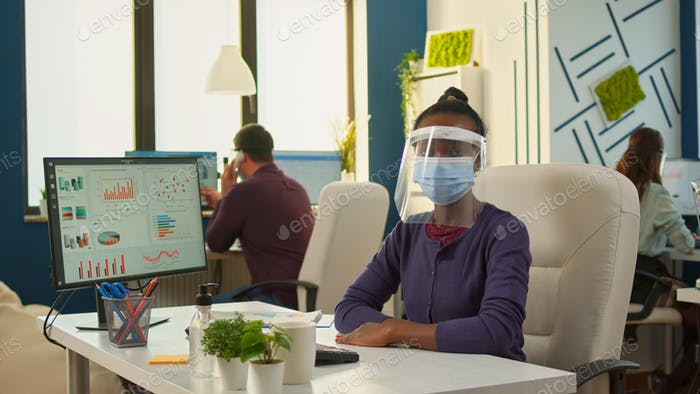Black employee with visor looking serious at camera