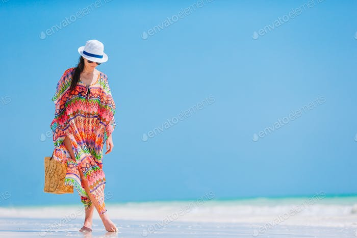 Young fashion woman in green dress on the beach