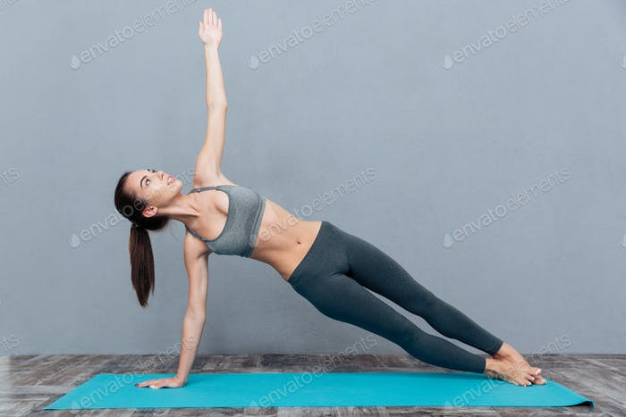 Young pretty woman in black sportswear practicing yoga