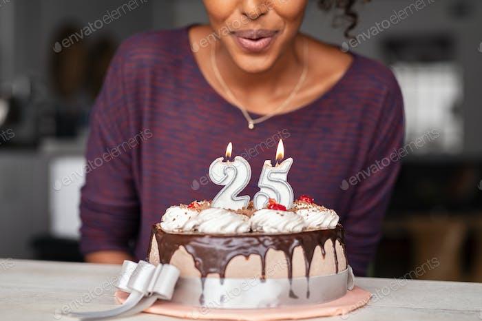 Afrikanische Frau bläst Geburtstagskerzen auf Kuchen