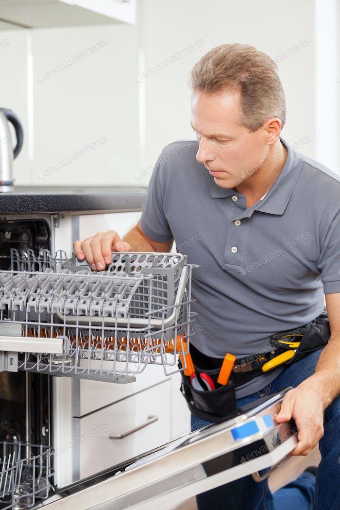 Handyman at work. Cheerful grey hair handyman working in a kitchen