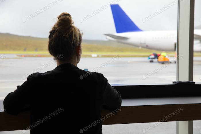 Woman Looking At Airplane Through Window At Airport