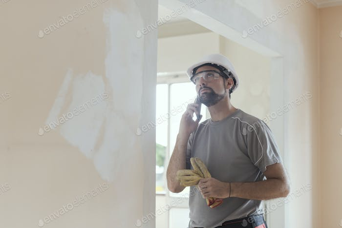 Professional builder working and having a phone call