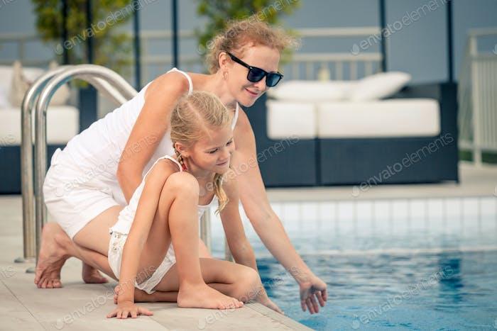 Mutter und Tochter entspannen in der Nähe von einem Schwimmbad am Tag ti