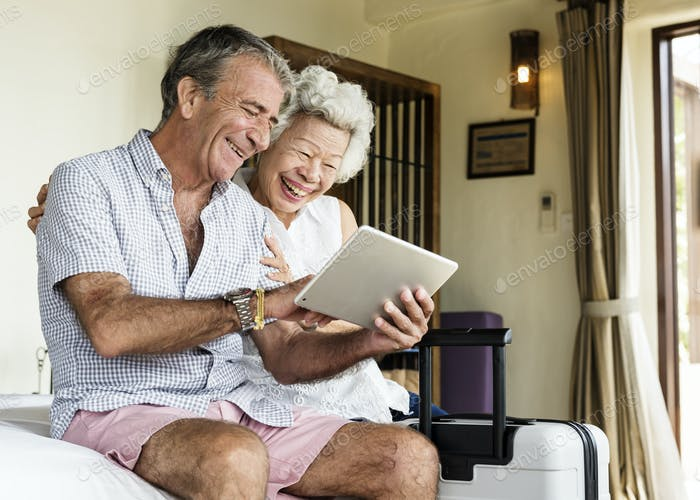 Senior couple using a tablet on the bed