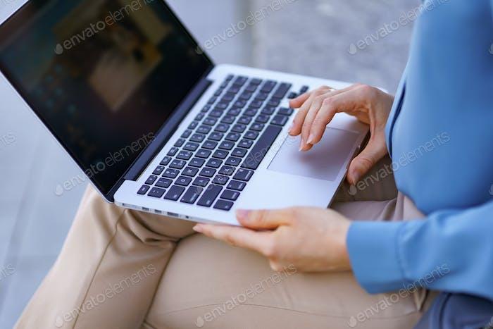 Weibliche Hand in der Nähe des Laptop-Touchpads im Freien