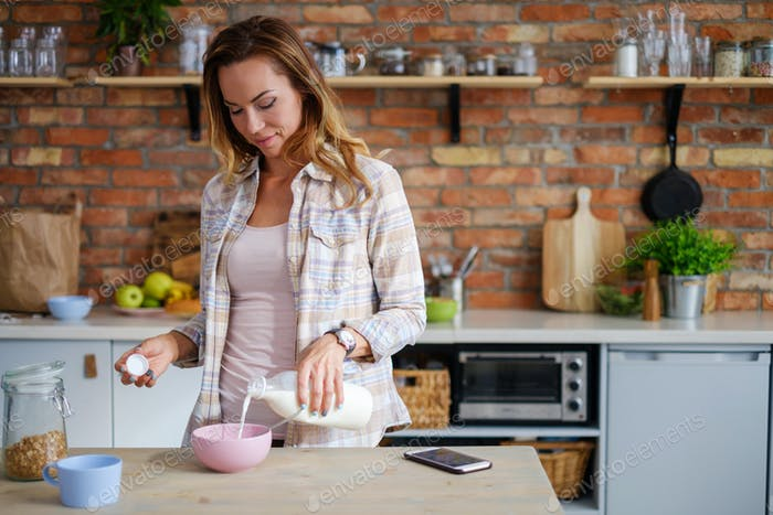 Woman making cereals for a breakfast
