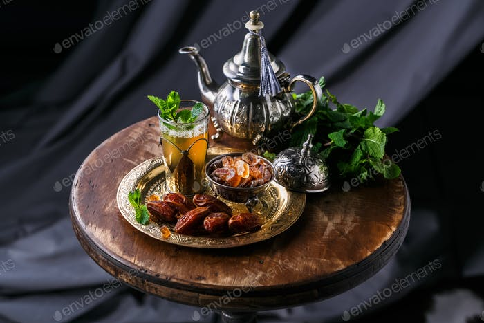 Glass of mint tea with dates and sugar, on copper plate