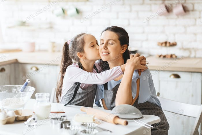 Little daughter kissing and hugging her mother in kitchen