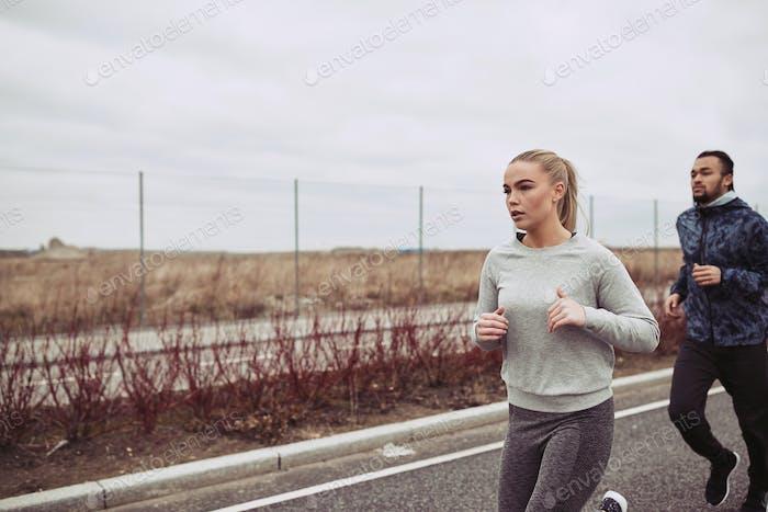 Молодая пара в спортивной одежде бег вместе вдоль загородной дороги