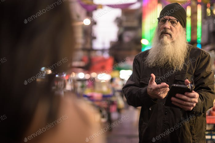 Mature bearded tourist man asking directions from young woman in Chinatown at night