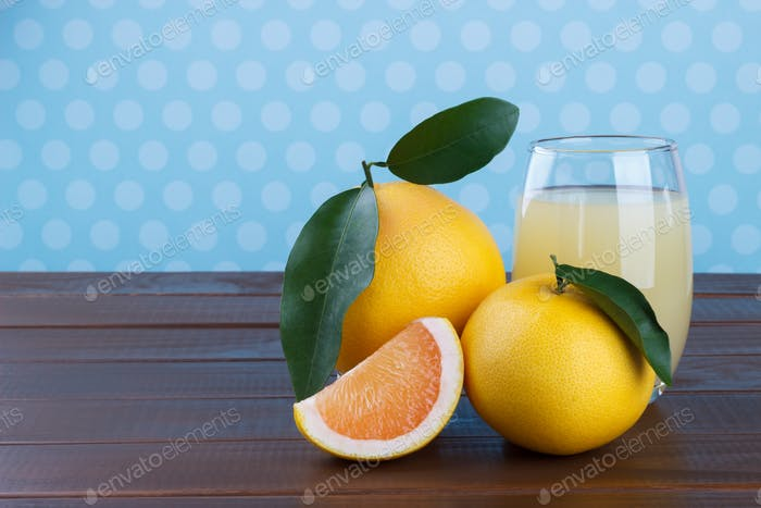 Grapefruit and juice on wooden table