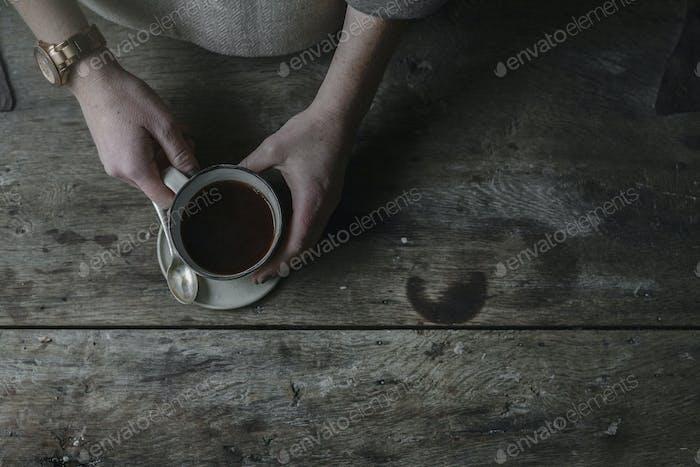 Eine Person, die eine volle Tasse aus einer Untertasse hebt.