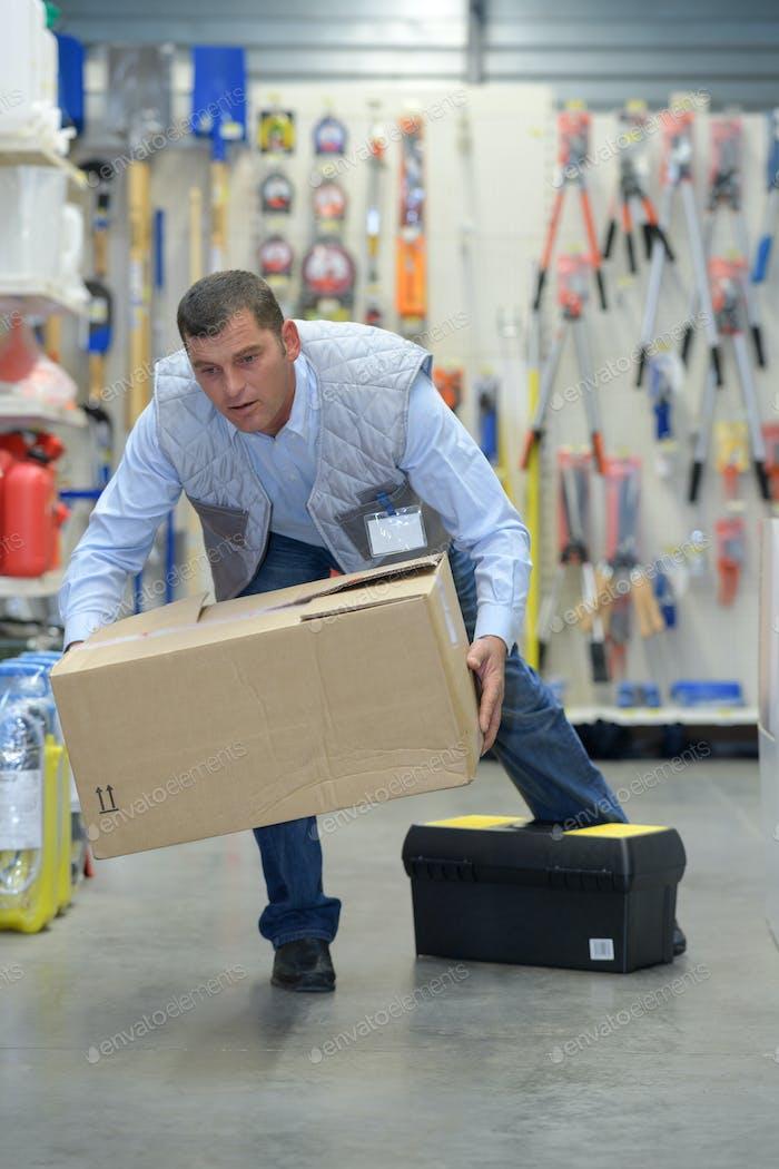 Man stumbling while carrying box