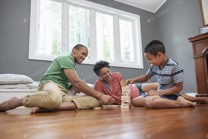 Family on the floor playing a game at home.