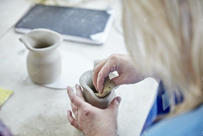 Eine Frau, die ihre Hände benutzt, um einen nassen Tonkrug zu formen und zu glätten, um einen anderen zu passen, ein Paar zu machen.