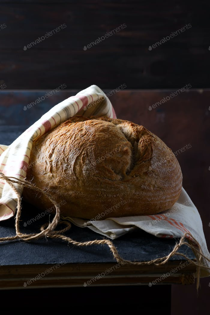 Freshly baked homemade rye bread decorated textile towel on a dark stone table