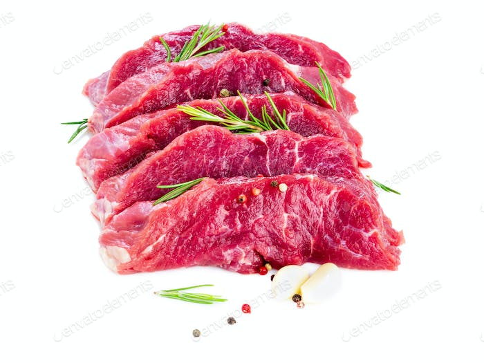 Raw meat, beef steak with seasoning on white background, side view