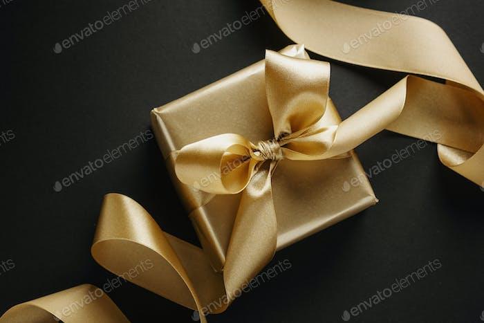 Caja de oro con cinta dorada en la oscuridad