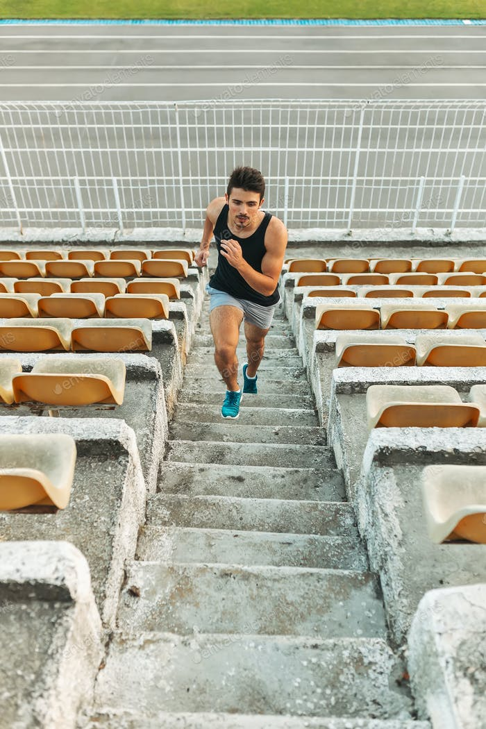 Image of young athletic man running by ladder at the stadium out