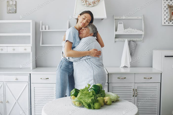 Old woman in a kitchen with young granddaughter